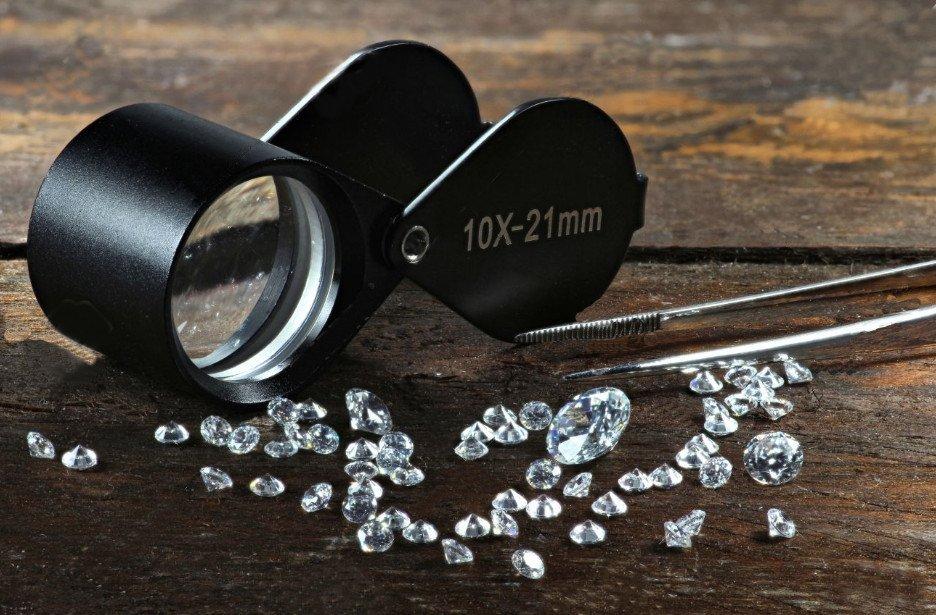 Mehrere geschliffene Diamanten mit Brillant-Schliff zur Bewertung für ihren Diamant-Wert vor Lupe und Pinzette