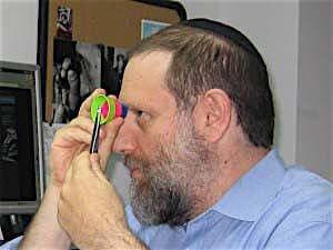 Brian Gavin schaut durch ein ASET auf einen Diamanten in einer Pinzette. Er macht seine Auswahl von Diamanten mit Fancy Cut