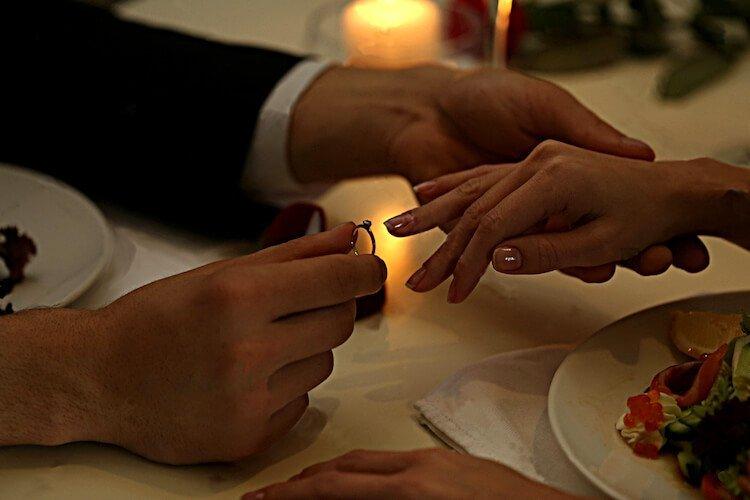 An einem Tisch bei Kerzenlicht steckt eine männliche Hand einen Diamantring an den Ringfinger von einer Frau - ohne Risiko einen Diamantring kaufen