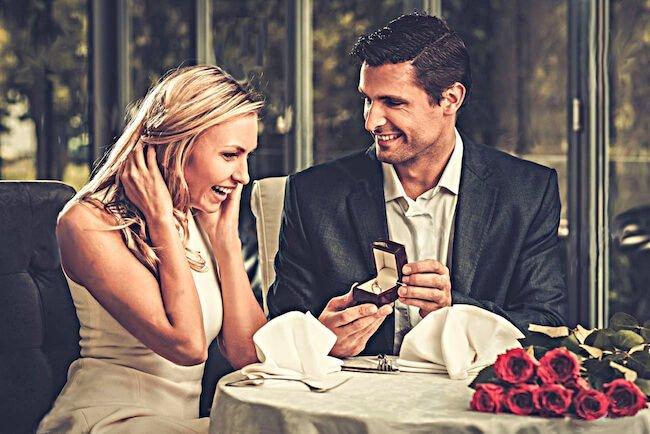 Die Überraschung ist perfekt. Das junge Paar sitzt in einem Restaurant. Ihr Freund hält das offene Schmuckkästchen mit einem Diamantring als Verlobungsgeschenk seiner hübschen Freundin entgegen