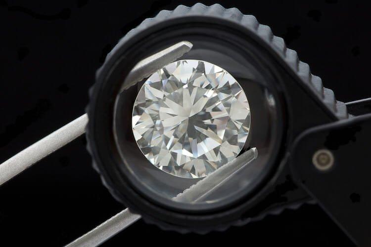 Diamanten Schliff unterschiedlicher Schliffgrade auf Bildern - Ein Diamant bei seiner Prüfung eingeklemmt in einer Pinzette