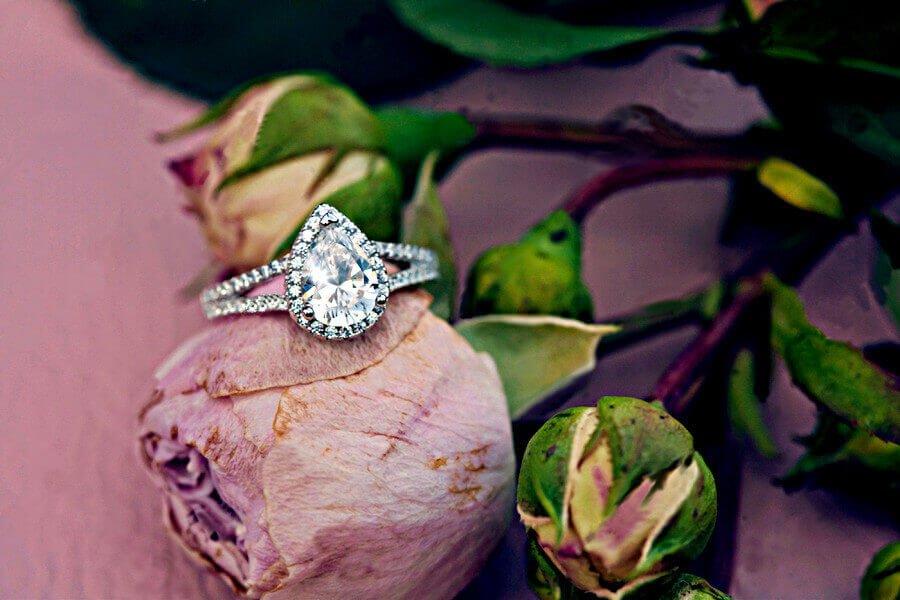 Halo Verlobungsing mit Hauptdiamant in Tropfenform auf pinkfarbener Rose - Übersicht über Verlobungsringe, ihre Konfiguration und Ring-Designs