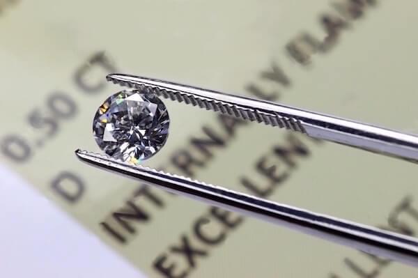 Pinzette hält einen Diamanten zwischen ihren Zangen über einem Diamantenzertifikat - Diamantenzertifikate